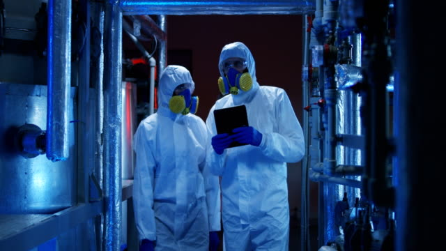 Scientists in hazmat suits conducting maintenance work