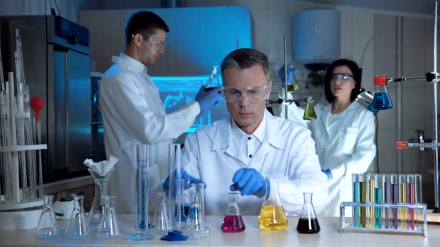 Scientists in laboratory doing experiments video