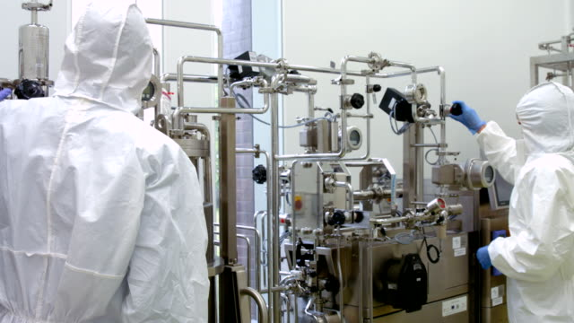 Scientists in protective suits working on vat video