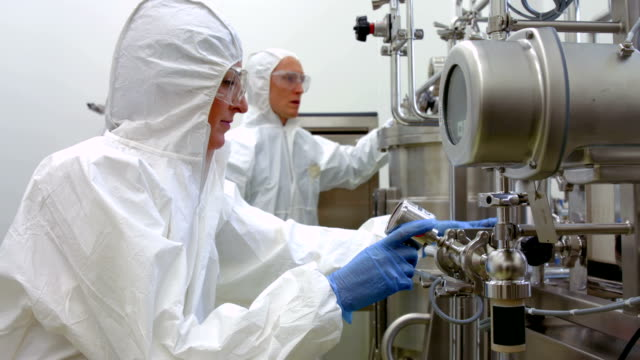 Scientists in protective suits working together video