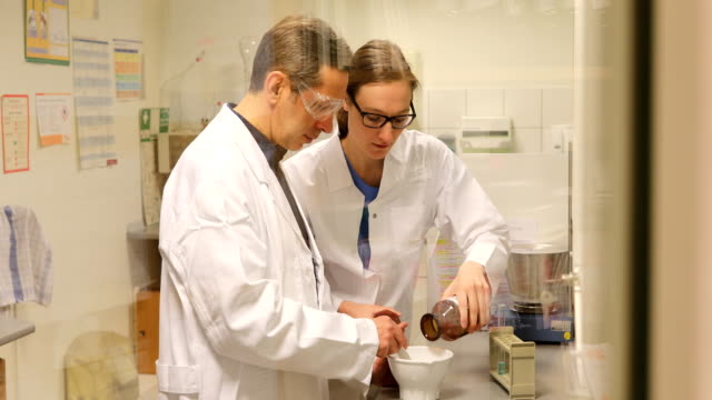 Scientists Making Medicine At Pharmacy Lockdown shot of scientists making medicine at laboratory. Male and female doctors working together are seen through glass wall. They are wearing lab coats at pharmacy. mortar and pestle stock videos & royalty-free footage