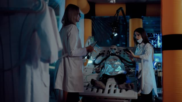 stockvideo's en b-roll-footage met wetenschappers van de ruimtelaboratorium zijn het bestuderen van de nieuwkomer uit de ruimte, kijkend naar zijn adem. alien ligt op de operatietafel, aangesloten op de sensoren en kunstmatige ademhaling apparaat. - ventilator bed