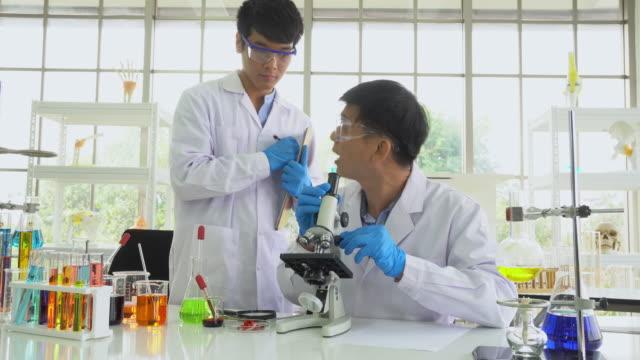 bilim adamları veya biyolog araştırma laboratuvarında çalışmak, panning atış - covid vaccine stok videoları ve detay görüntü çekimi