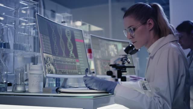 vídeos de stock, filmes e b-roll de cientistas estudando mutações de dna. telas de computador com hélice de dna - equipamento médico