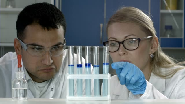 Scientists studying substance in test tubes in lab video