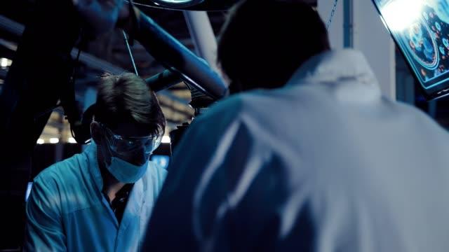 vídeos y material grabado en eventos de stock de los cirujanos científicos discuten la operación. los hombres están vestidos con batas blancas y vasos, trabajando en el laboratorio científico de la nave espacial. - autopsia