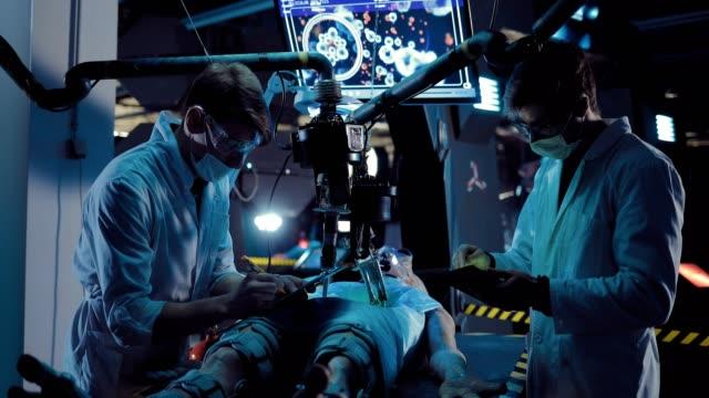 vídeos y material grabado en eventos de stock de los cirujanos de los científicos observan el funcionamiento de un alienígena. el recién llegado miente en la tabla de funcionamiento, la autopsia se lleva a cabo con la ayuda del equipo. - autopsia