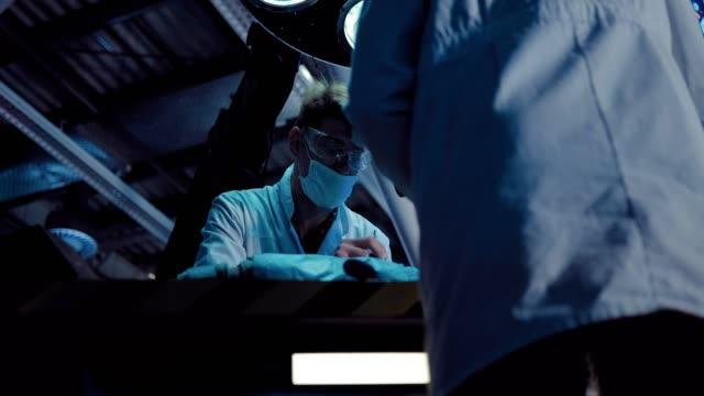 vídeos y material grabado en eventos de stock de científicos cirujanos trabajando en una autopsia. los doctores llevan batas y anteojos blancos, una unidad operativa de laboratorio. - autopsia