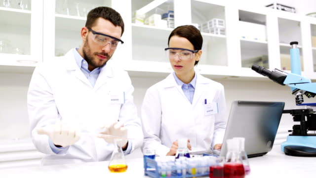scientists with pipette and glass making test or research at laboratory - occhiali protettivi video stock e b–roll