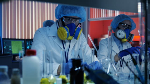 Scientists working in laboratory Medium shot of scientists mixing liquid and powder in laboratory occupational safety and health stock videos & royalty-free footage