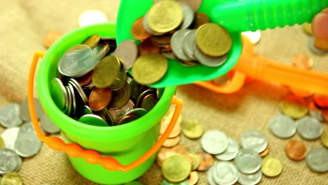 scooping-münze mit kunststoffschaufel gießen zu eimer - eimer stock-videos und b-roll-filmmaterial