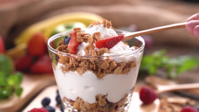 vídeos de stock e filmes b-roll de scooping yogurt with granola and fruits - granola