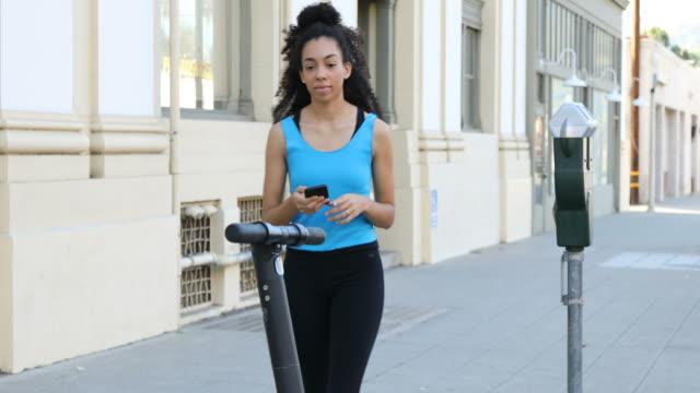 scooter woman approaches - monopattino elettrico video stock e b–roll