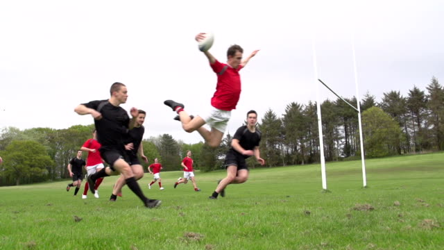 Scoring a diving try in Rugby match (Sport) Slow Motion Stock HD video clip footage of a Rugby player scoring a try under the posts. There are two teams, the red rugby team are attacking, the black team are defending. The player performs a huge swan dive and carries the rugby ball over the line to score a try. Filmed outdoors. Great sports action clip, perfect for the Rugby world cup. rugby stock videos & royalty-free footage