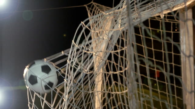 Scoring GOAL with soccer ball / football - Super Slow Motion Stock HD video clip footage of a goal being scored in the net during a football match. There are floodlights on as the ball hits the back of the net in between the goalposts. Filmed in Super slow motion scoring a goal stock videos & royalty-free footage