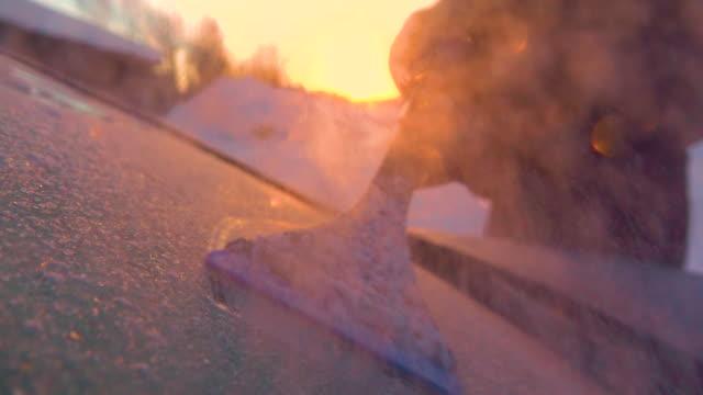 slow motion raschiare il gelo dell'auto da un finestrino di un'auto fiocchi di neve ghiacciati che scorrono nella telecamera - brina ghiaccio video stock e b–roll