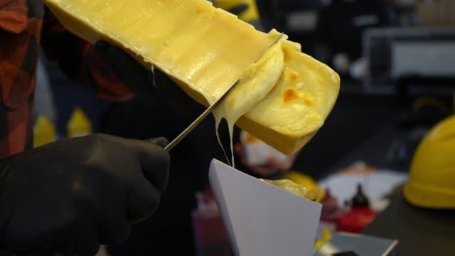 vidéos et rushes de grattant le fromage à raclette suisse traditionnel fondu - raclette