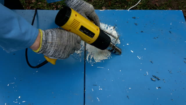 Scraping removing old blue paint from old wooden cupboard