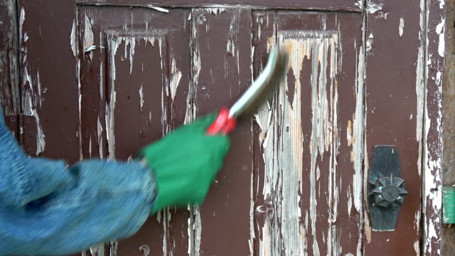 Scraping removing old  paint from wooden door