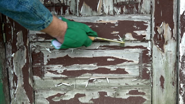 Scraping removing old  paint from wooden door with scraper