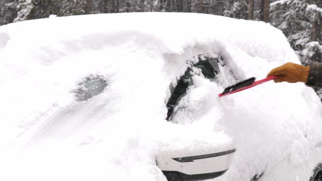 vidéos et rushes de racler les vitres de la voiture en hiver neige - pare brise
