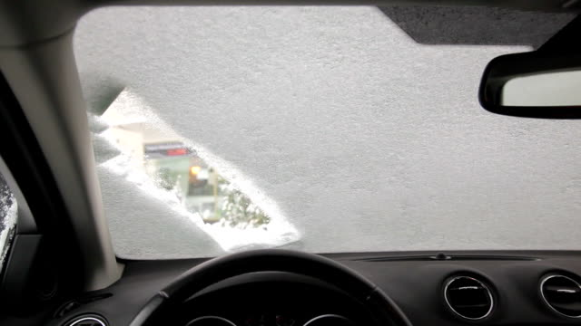 scraping the ice of a car windshield 1080p video