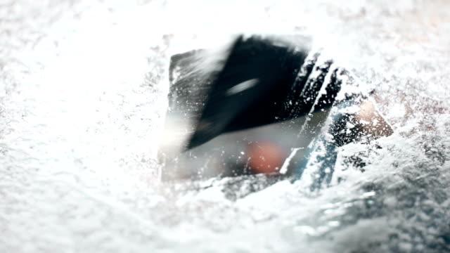 vidéos et rushes de gratter la glace sur le pare-brise d'une voiture - raclette