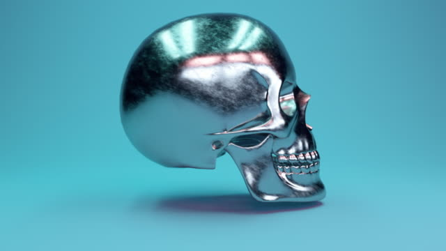 A scratched metal human skull rotates 360 degrees against a glamorous blue background. Seamless loop 3d render video