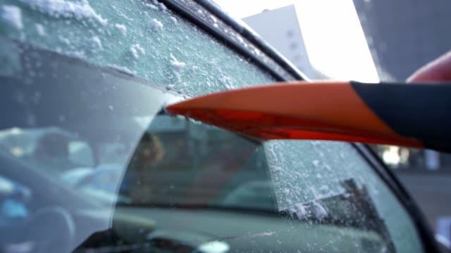 vidéos et rushes de glace de grattage de la fenêtre congelée de voiture avec le mouvement lent orange de grattoir de glace - raclette
