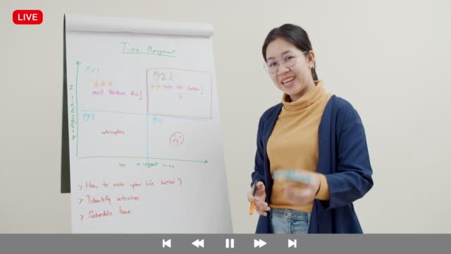 interfaccia dello schermo dell'insegnante asiatica che parla e insegna per l'educazione online durante l'auto-isolamento dal coronavirus. istruzione online per l'apprendimento a distanza nuovo concetto normale - didattica a distanza video stock e b–roll