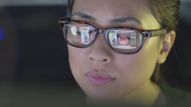 Screen reflections medical Close up stock video clip of a young Chinese asian woman intently studying computer monitors showing medical data: MRI scans; x rays; CAT scans….some of these images are movies & they're all clearly reflected in the glasses she's wearing. radiologist stock videos & royalty-free footage