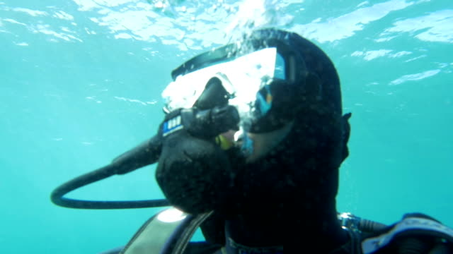 Scuba diver in blue water on sunny day Slow motion of scuba diver underwater close to surface. When he looking up sun reflecting in his mask aqualung diving equipment stock videos & royalty-free footage