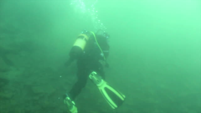Scuba diver in dry suit diving english lake in winter Scuba diver in dry suit diving english lake in winter aqualung diving equipment stock videos & royalty-free footage