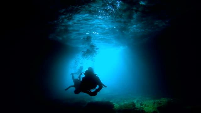 vidéos et rushes de les plongeurs peuvent explorer une grotte sous-marine - plongée sous marine