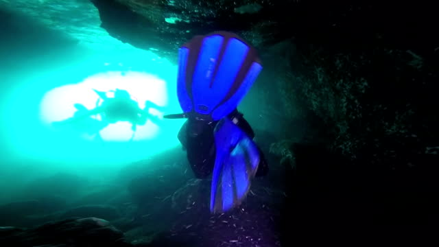 Scuba Divers In An Underwater Cave Silhouettes of Scuba Divers swimming, with sun rays in a cave. aqualung diving equipment stock videos & royalty-free footage