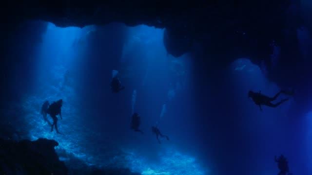 scuba diving in dark cavern, blue hole, palau - подводное плавание с аквалангом стоковые видео и кадры b-roll
