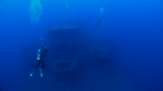 Scuba diving in the shipwreck at deep sea video
