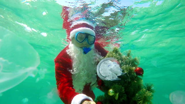 Scuba Santa Claus under water installs Christmas tree on seabed video