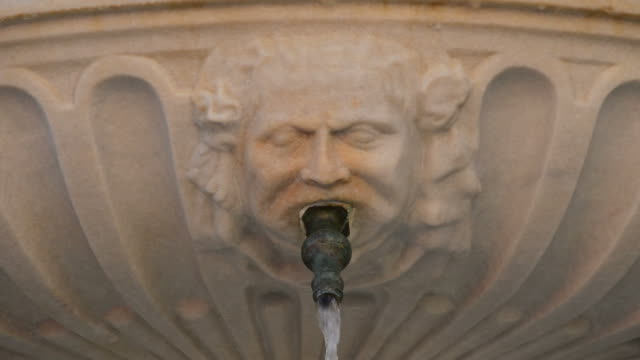 Sculpted face mouth in a fountain pouring water video
