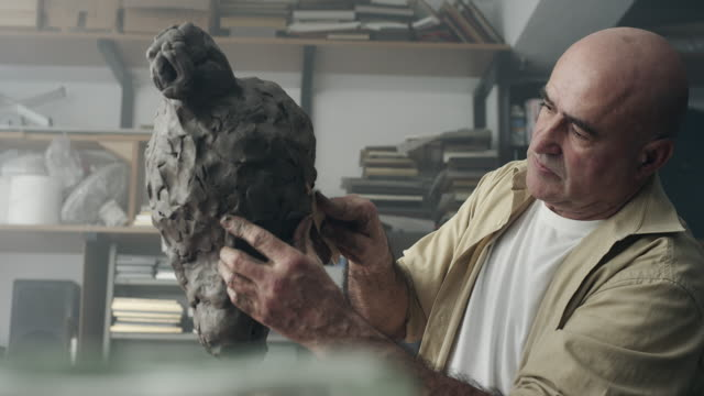 scultore crea una scultura in argilla - scultura video stock e b–roll