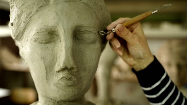 sculptor modelling sculpture adjusting face details