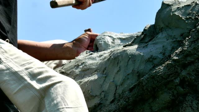 stockvideo's en b-roll-footage met beeldhouwer verwerkt steen met een beitel en hamer - marmer