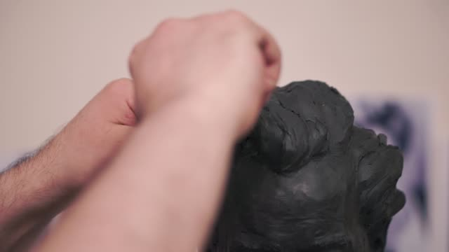 A sculptor who works on his clay sculpture in his workshop. Clip. Man cuts a mold of clay video