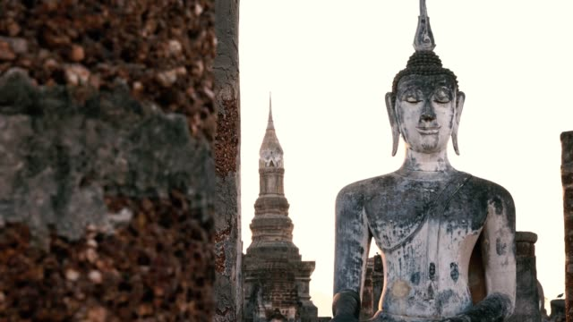 Sculpture standing buddha image of Wat Mahathat in the National Park of Sukhothai in Thailand at sunset. Travel to Asia and holidays concept. Buddhist religion, ancient art and asian heritage culture. sukhothai stock videos & royalty-free footage