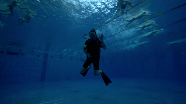 Sdiver in diving mask and diving equipment swimming underwater deep pool Man scuba diver in diving mask and diving equipment swimming underwater deep pool. Scuba diving in swimming pool. Scuba diver face underwater closeup aqualung diving equipment stock videos & royalty-free footage