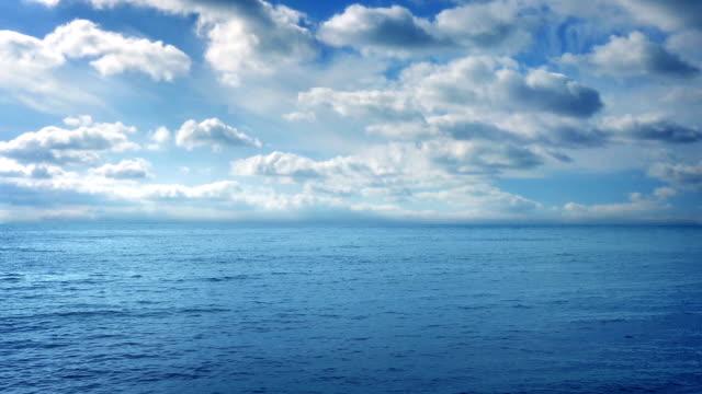 vídeos de stock, filmes e b-roll de mar e céu azul em dia ensolarado - largo descrição geral