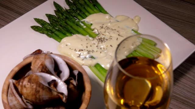 vídeos de stock, filmes e b-roll de caracóis do escargo do mar com espargos e vinho branco - comida salgada