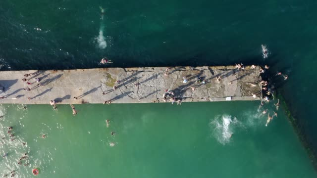 sea from above. People swimming jumping from the pier to the water. - video