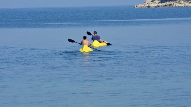 sea kayak. People having fun rowing at open sea video
