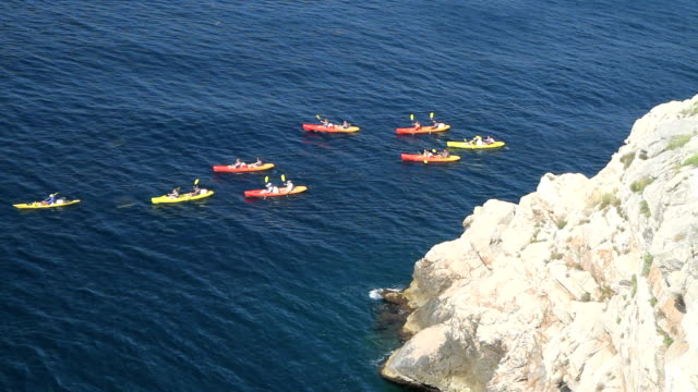 Sea Kayaking in Dubrovnik Coratia Large group of kayaks come around a rocky edge in Dubrovnik, Croatia.  Shore birds swoop in circles in the foreground. diving to the ground stock videos & royalty-free footage